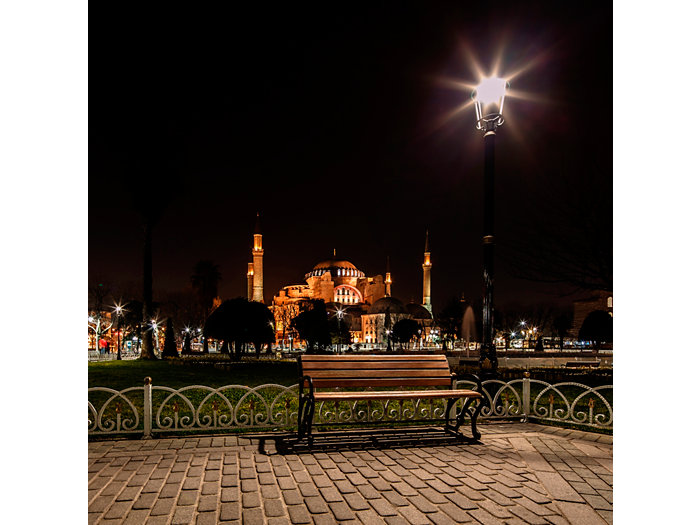 Application picture of TrueForce post-top urban lighting at night outside with mosque on the background. Lamppost with bench