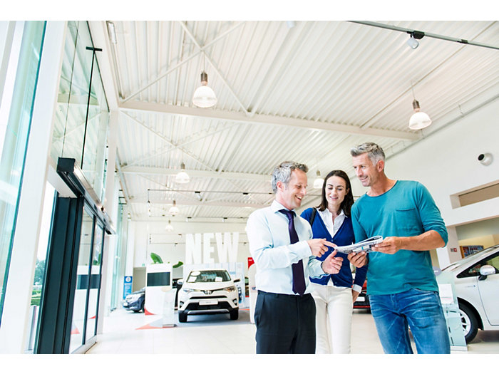 Application picture of MASTERColour CDM MW eco at  car dealership with 3 people discussing something in a brochure