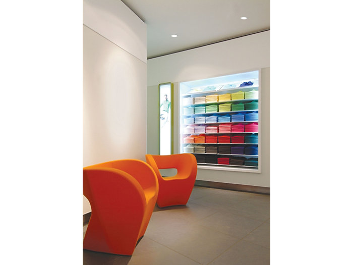 Application picture of MASTER LEDspot. Retail clothing store with two orange design-modern chairs. Shelves with shirts in different colors in the background.