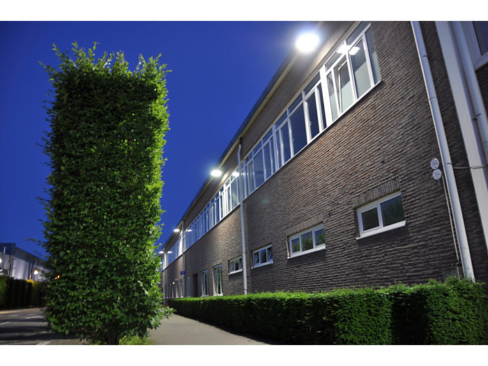 Application picture of MASTERColour CDM MW eco outside in the evening in a industrial area with big green hedge the building has big bright lights underneath the gutter