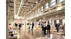 Application picture of MASTERColour CDM MW eco at  an art exhibition, industrial building. Groups of people everywhere looking at the art pieces. Big industrial luminaires